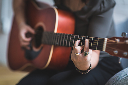closeup of woman playing guitar